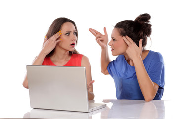 Two young women arguing behind the laptop