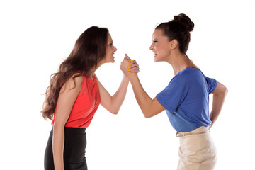 Two women wrestling with hands clasped