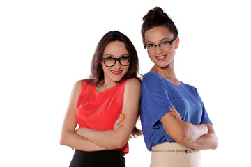 Two happy girls with glasses standing with arms folded