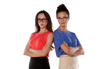 Two girls with glasses standing with arms folded