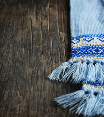 Knitted scarf on wooden background. Selective focus