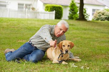 Älterer Mann mit Hund im Garten