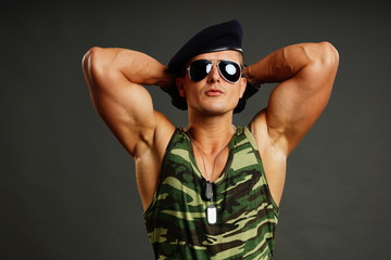 Muscular young military man poses with his hands behind the head
