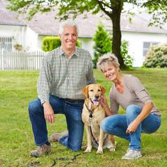 Paar Senioren im Garten mit Hund