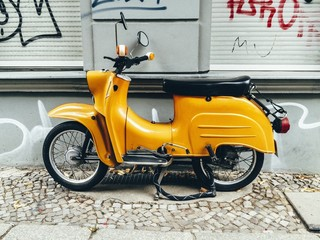 old yellow motor scooter parked on pavement on Mitte, Berlin