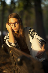 Girl Sitting On Bench In Park Looking At Sun