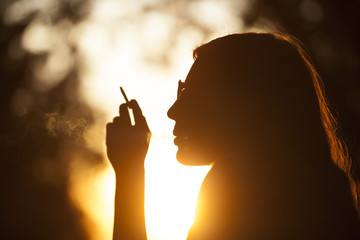 Girl Smoking At Sunset In Park Outdoor