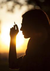 Girl Smoking at sunset in park
