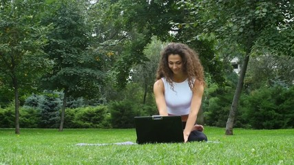 Young woman yoga in the park working on a laptop