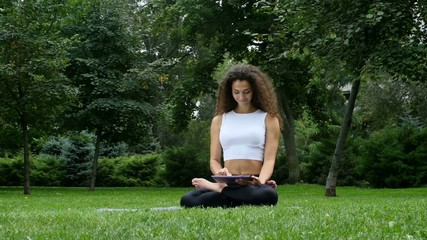 Young woman yoga in the park working on a tablet pc