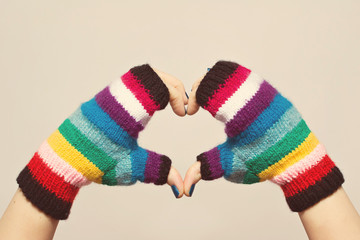 Female hands in colorful knitted gloves gesturing heart