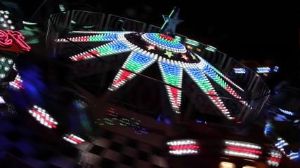 Beleuchtetes Fahrgeschäft auf dem Volksfest