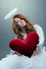 Cute girl in angel costume posing with teddy heart