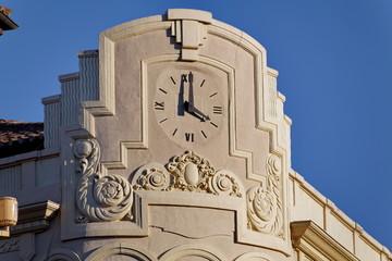 Horloge sur façade arrondie en pierre blanche.