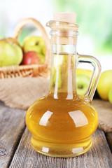 Apple cider vinegar in glass bottle and ripe fresh apples,