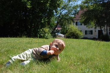Baby liegt im Garten eines Hauses mit grünen Fensterläden
