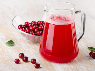 Cranberry drink with fresh berries on a wooden background