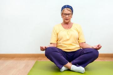 Elderly woman practising yoga in gym.