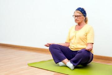 Senior woman meditating in gym.