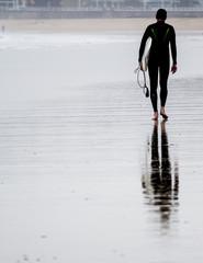 Surfista paseando por la orilla
