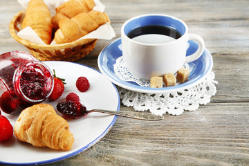 Breakfast with tea, raspberry jam and fresh croissants