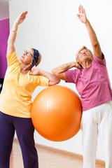Senior women stretching with gym ball.