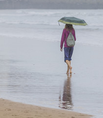 Chica con paraguas paseando por la orilla de la playa
