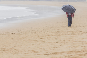 hombre con paraguas paseando por la playa