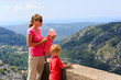 mother with kids looking at scenic view in mountains
