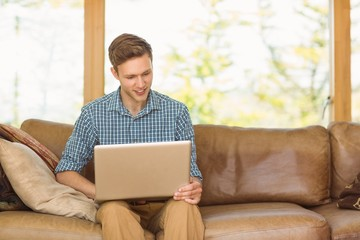 Young man relaxing on his couch with laptop