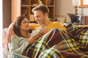 Young couple cuddling on the couch under blanket