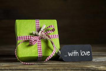 Ein apfelgrünes Geschenk mit rot weiß karierter Schleife