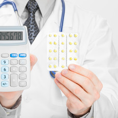 Doctor with calculator and pills in hands - 1 to 1 ratio
