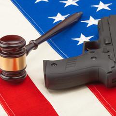 Gun and judge gavel above USA flag - 1 to 1 ratio