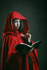Red hooded woman reading a book