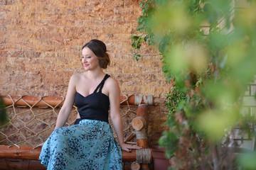 Beautiful young woman wearing long dress, sitting on a bench