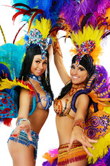 Two smiling beautiful girls in a colorful carnival costume