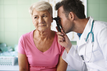 Doctor examining ear of senior woman