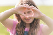 girl making a love heart sign