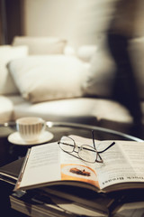 Living room sofa with coffee table book eyeglasses and people
