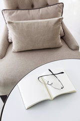 Armchair in living room pillow with book and eyeglasses on the t