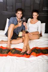 Junges Paar mit Wein im Hotelbett