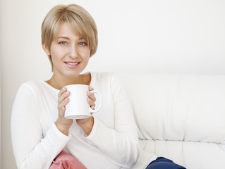 beautiful woman with a cup on a white couch