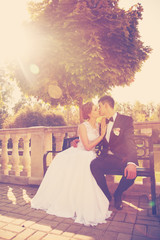 attractive bride and groom kissing, sitting on a bench