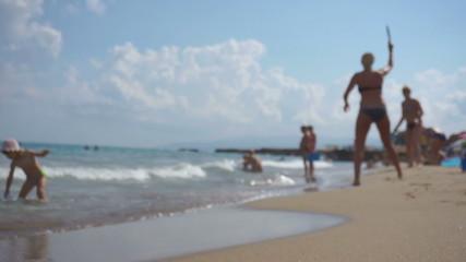 Silhouette girls play beach leisure tennis game. Defocus.