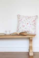 Wooden bench with coffee book and pillow