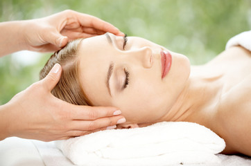Woman relaxing at a spa having a facial
