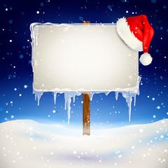 Wegweiser mit Nikolausmütze im Schnee