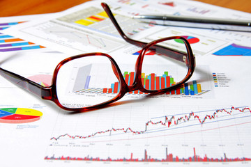 Glasses and pen on business chart