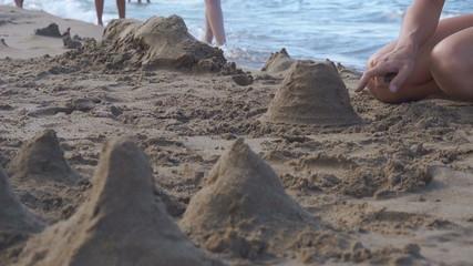 Builds sand castle on the beach.